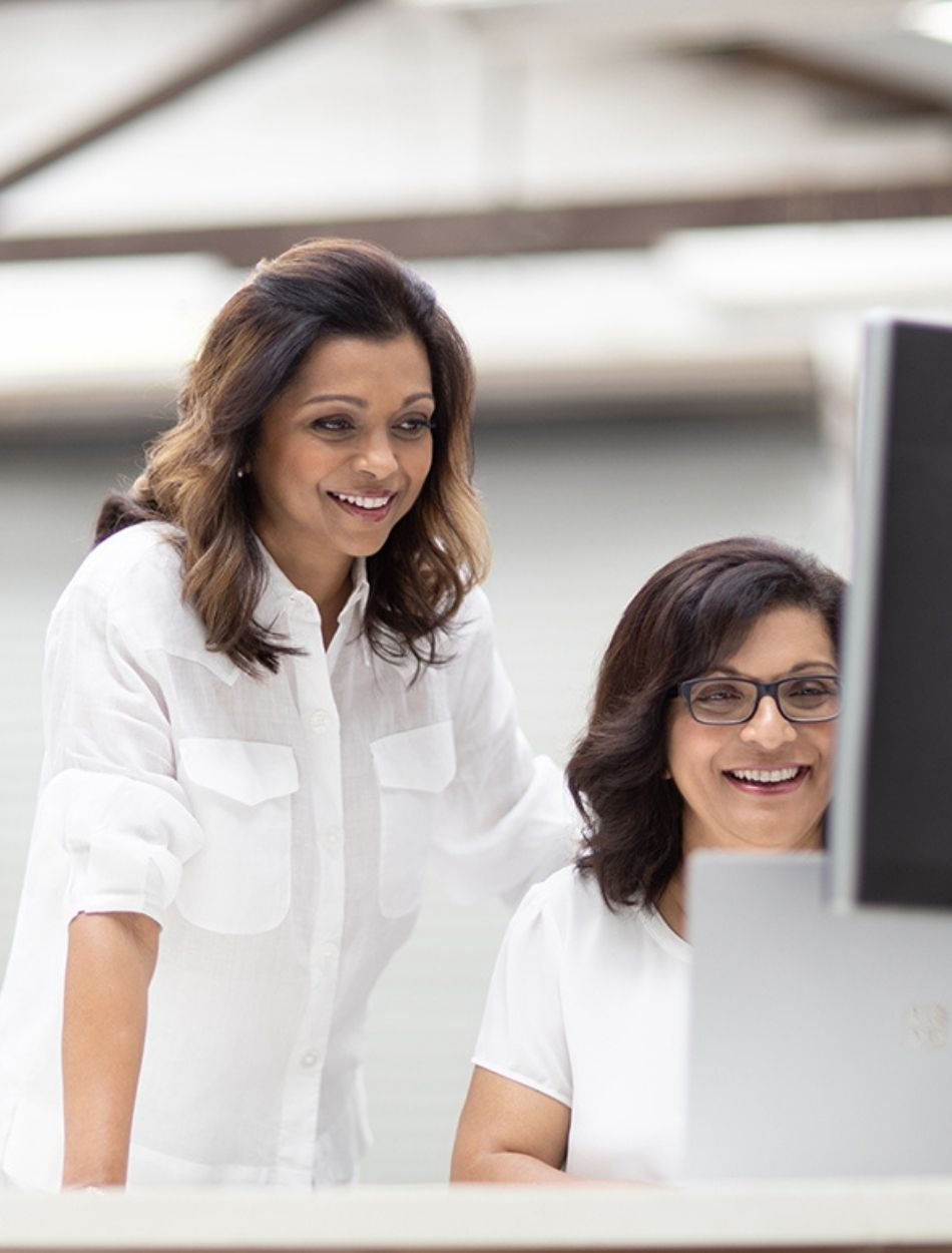 Giraffe App - Creators Vas Nair and Sobha Nair looking over a computer screen. Both are dressed in white shirts with Vas standing over Sobha's shoulder
